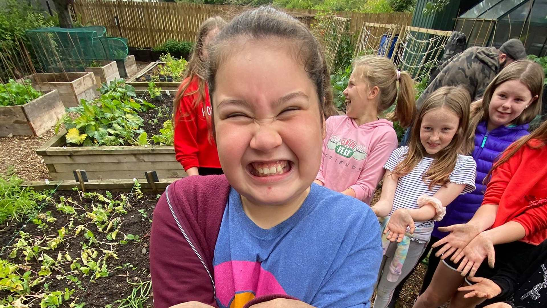 A child smiling and showing her muddy hands to the camera in a community garden
