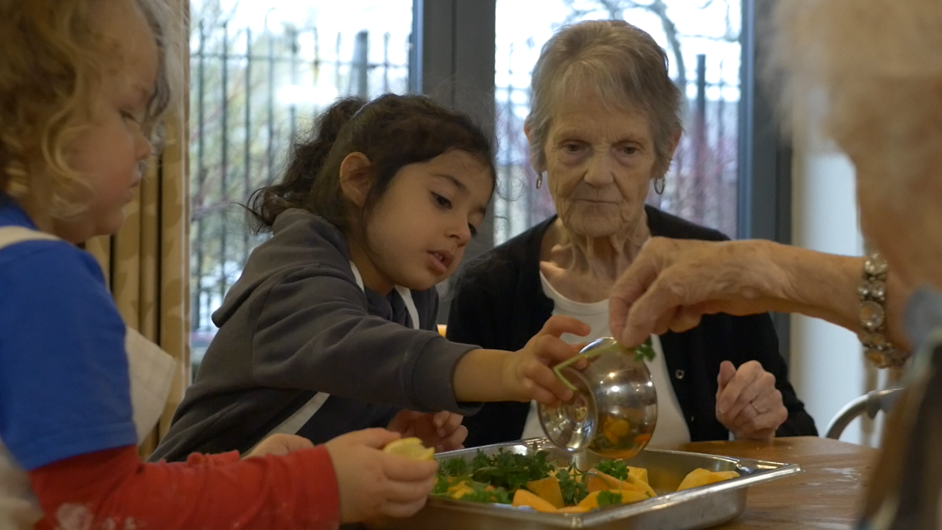 Older people and early years children cooking together