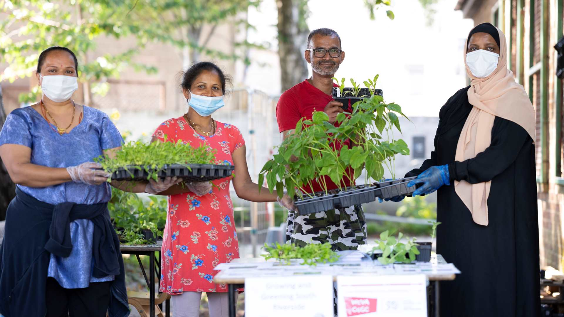 A woman in a face mask handing out plants to community members