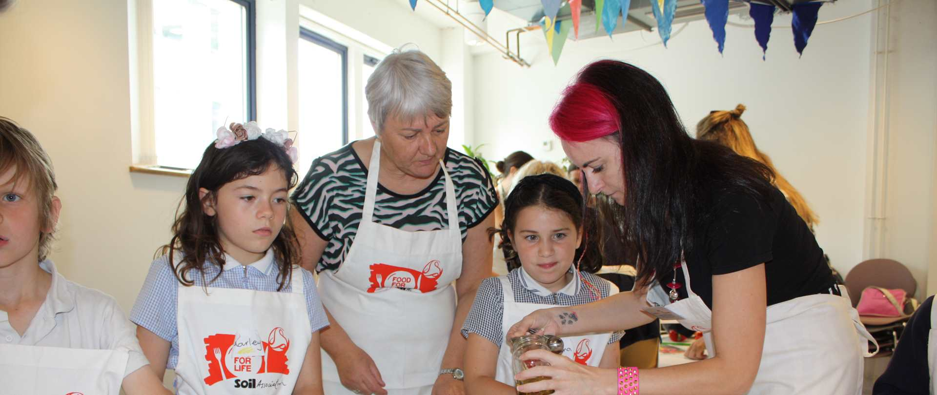 Tow adults and three children wearing Food for Life aprons cooking together