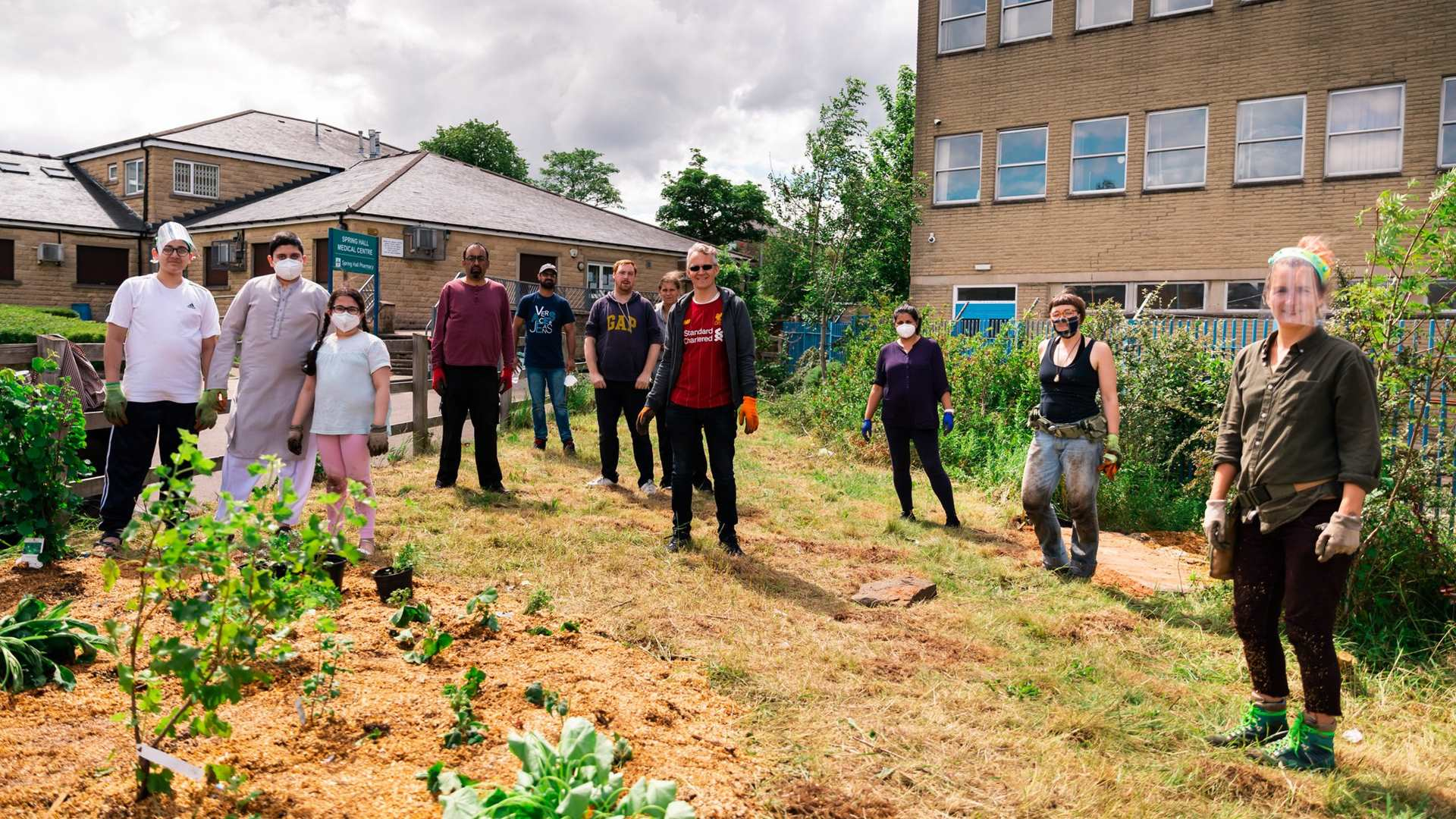 Group of people wearing masks and PPE standing at a distance from one and other in a community garden