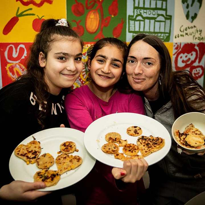 A woman and two children display food they have cooked from scratch