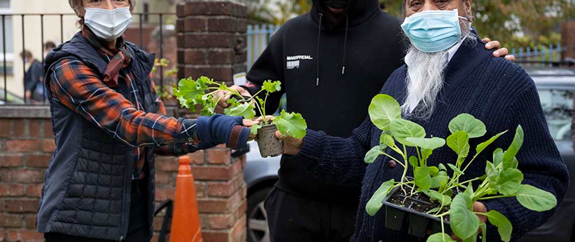 Three people sharing plants wearing Covid-19 safe masks