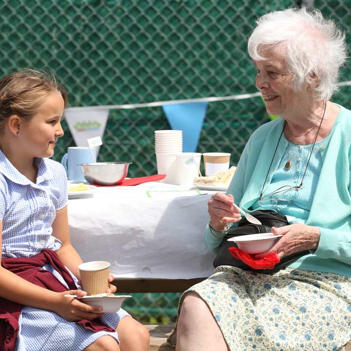 An older person and a child in school uniform enjoying a meal together