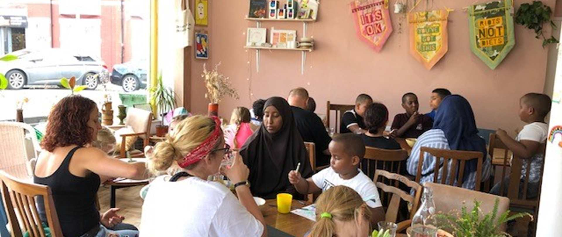 A group of children and adults enjoying a meal together at a community cafe