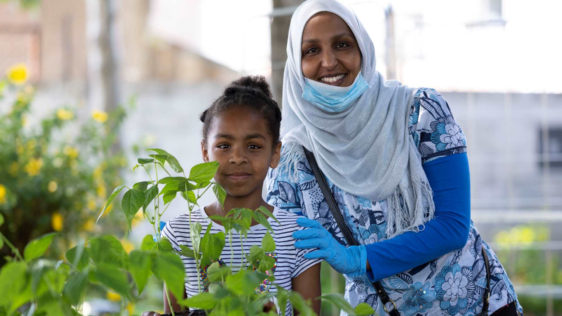 Woman wearing a headscarf with a child standing behind plants and smiling