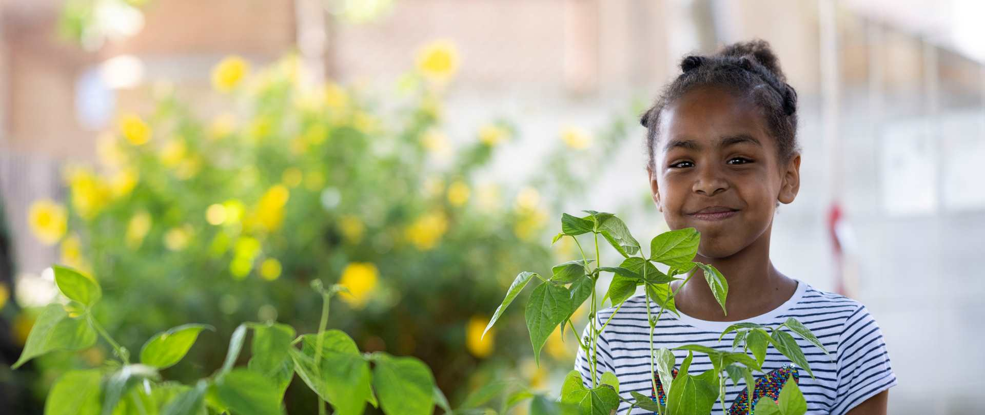 Child smiling in a greenhouse