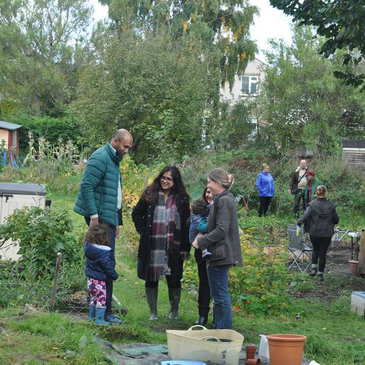 Group of adults with children talking in a community garden